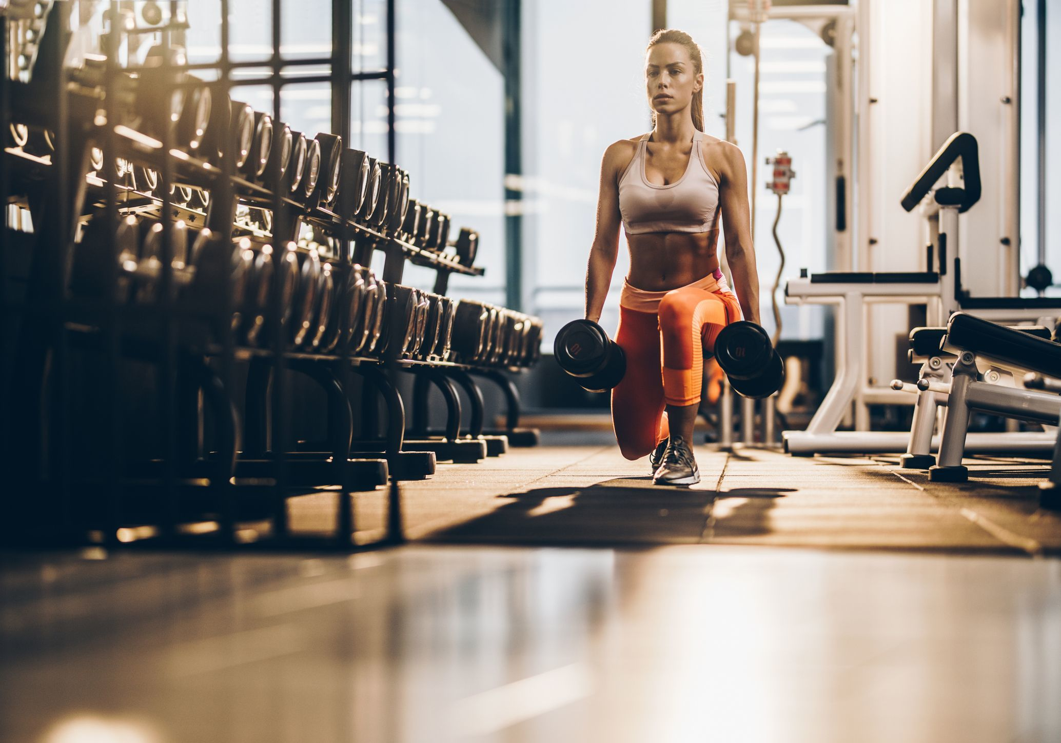 female athlete exercising with dumbbells in a lunge royalty free image 909891594 1558710148 1ae4c