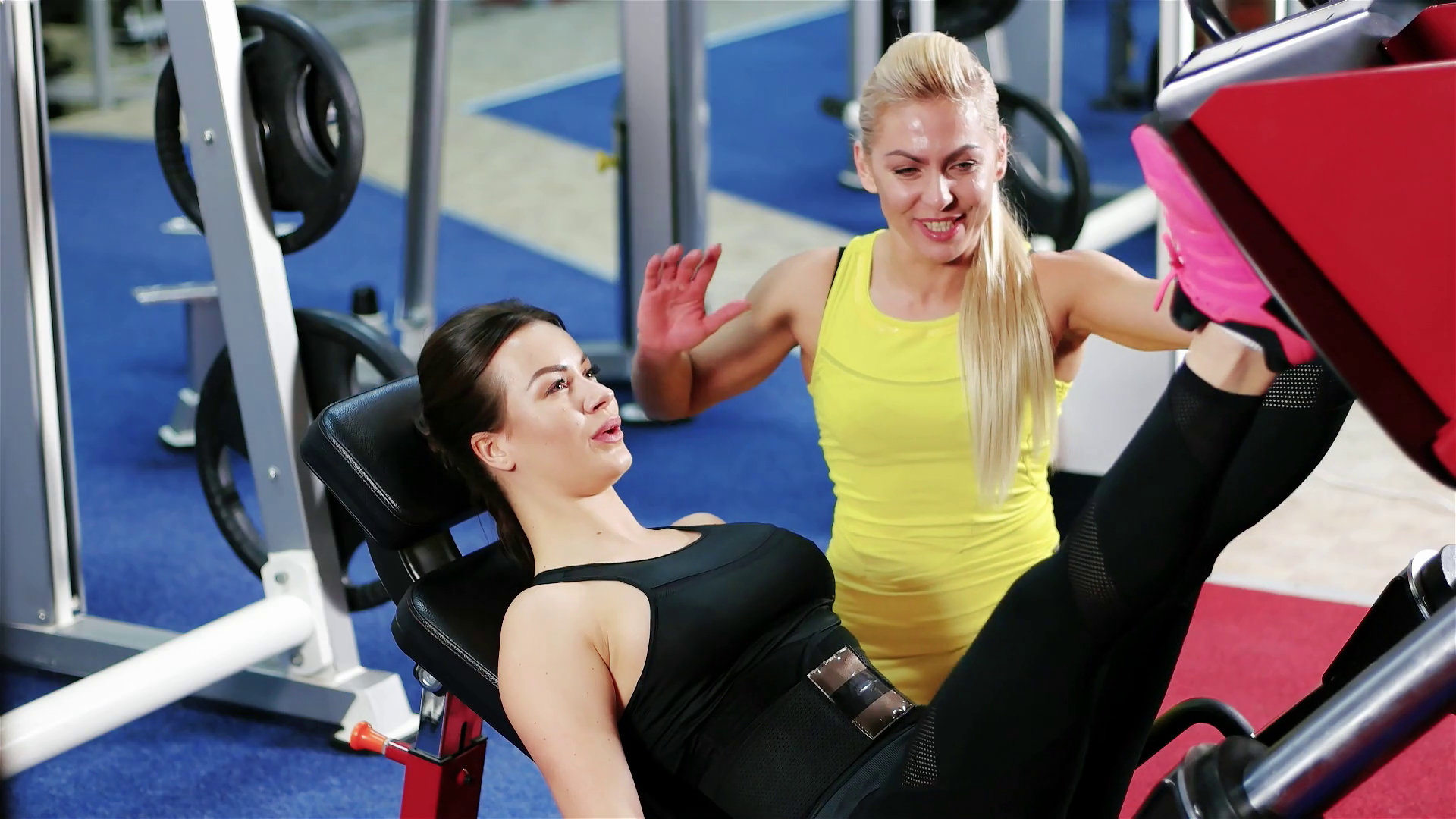 trainer helps the woman to perform strength exercises workout with simulator leg press in the gym girl is engaged in fitness with the coach in the gym htgclslftg thumbnail full01 9f351